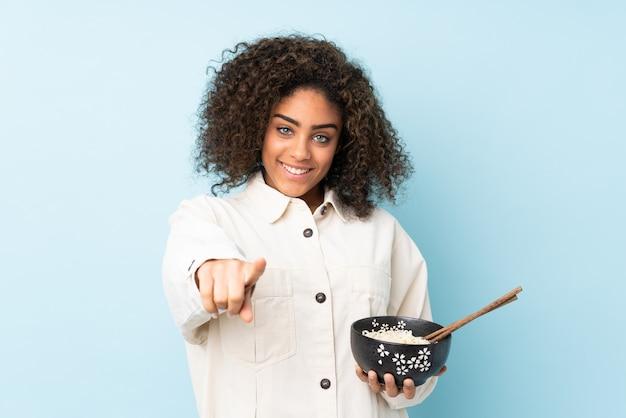 Молодая афроамериканская женщина, изолированная на синих точках пальцем на вас с уверенным выражением, держа миску лапши с палочками для еды