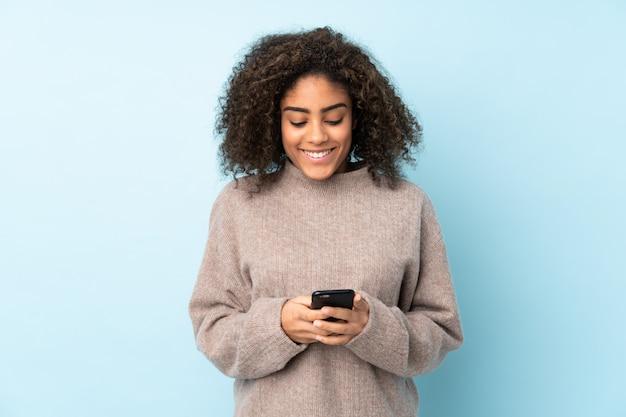 Молодая афроамериканец женщина, изолированных на синем, отправив сообщение с мобильного телефона