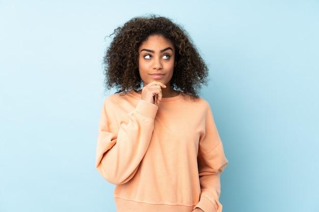 Молодая афро-американская женщина изолированная на сини думая идея пока смотрящ вверх