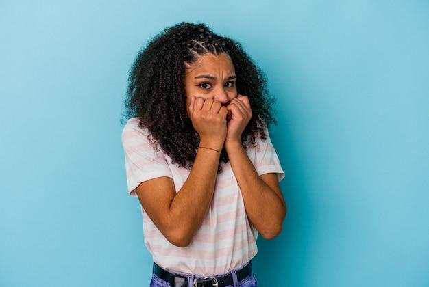 Молодая афро-американская женщина изолирована на синей стене, кусая ногти, нервная и очень взволнованная