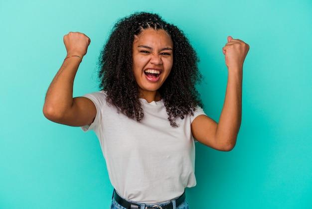 のんきと興奮して応援している青い壁に孤立した若いアフリカ系アメリカ人の女性。利佳國際電子。