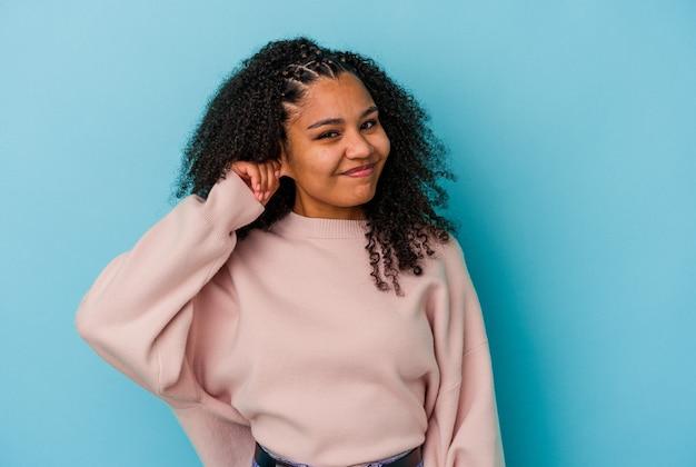 若いアフリカ系アメリカ人の女性は、指で耳を覆っている青い壁に孤立し、大声で周囲にストレスを感じ、必死になっています。