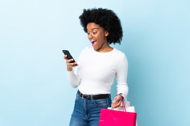 Молодая афро-американская женщина изолированная на голубой стене держа хозяйственные сумки и писать сообщение с ее сотовым телефоном к другу