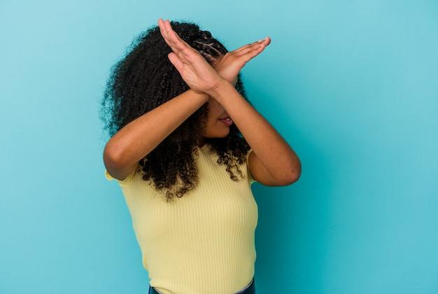 두 팔을 유지하는 파란색 벽에 고립 된 젊은 아프리카 계 미국인 여자 넘어, 거부 개념.