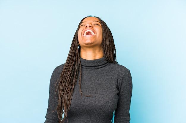 Молодая афро-американская женщина, изолированная на голубой стене, расслабилась и счастлива смеясь, вытянув шею, показывая зубы.