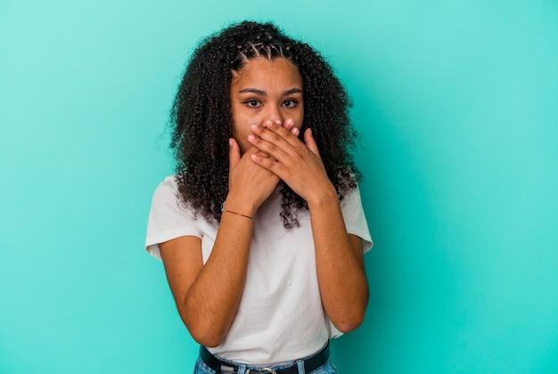 青い壁に孤立した若いアフリカ系アメリカ人女性はショックを受け、手で口を覆い、何か新しいものを発見することを切望していました。