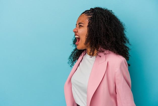 非常に怒っている、怒りの概念、欲求不満を叫んで青い壁に孤立した若いアフリカ系アメリカ人の女性。