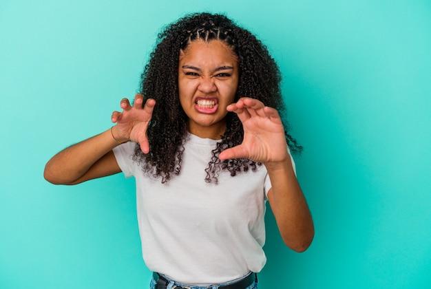 猫を模倣した爪、攻撃的なジェスチャーを示す青い壁に分離された若いアフリカ系アメリカ人女性