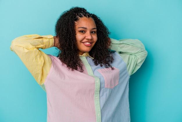 Молодая афро-американская женщина, изолированные на синей стене, протягивая руки, расслабленное положение.