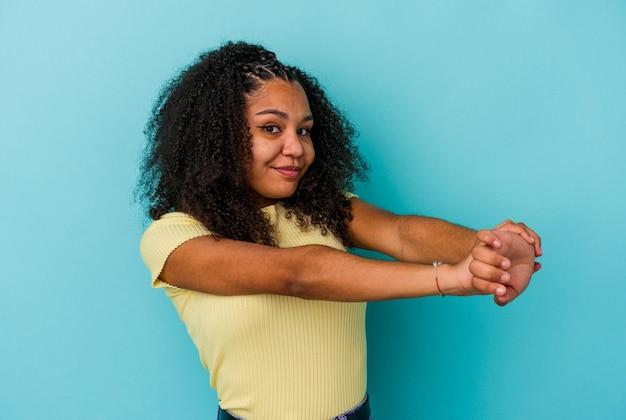 Молодая афро-американская женщина изолирована на синей стене, протягивая руки, расслабленное положение
