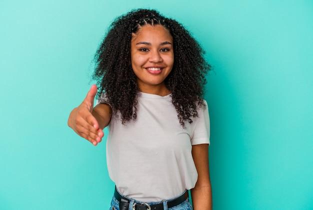 Молодая афро-американская женщина изолированная на голубой стене протягивая руку в жесте приветствия.