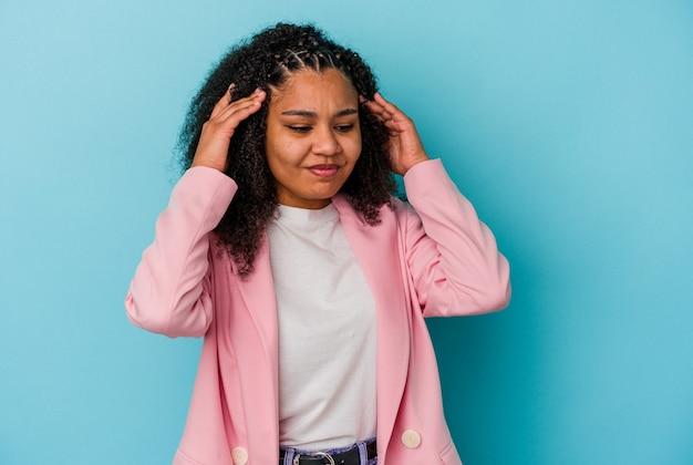 こめかみに触れて頭痛を持っている青い壁に孤立した若いアフリカ系アメリカ人の女性。