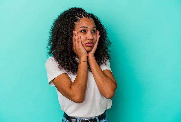 파란색 벽 징징이 고 절망적으로 울고에 고립 된 젊은 아프리카 계 미국인 여자.