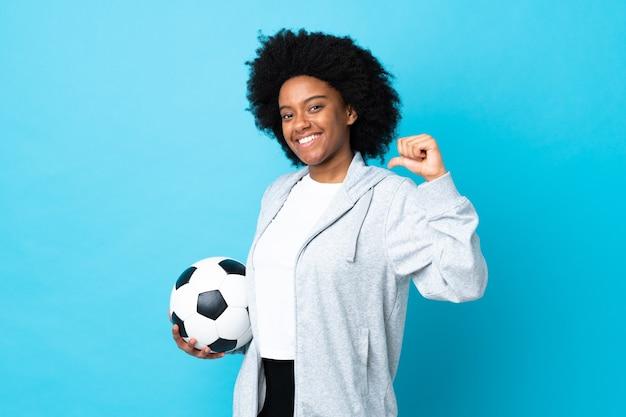 Молодая афроамериканка изолирована на синем с футбольным мячом и гордится собой