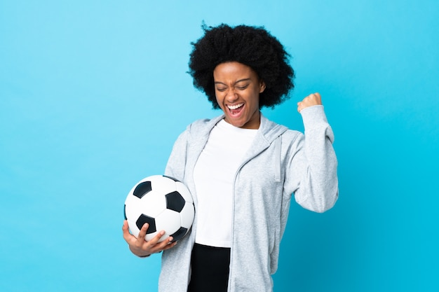 勝利を祝うサッカーボールと青に分離された若いアフリカ系アメリカ人女性