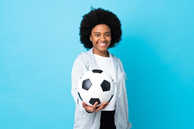 Молодая афро-американская женщина изолирована на синем с футбольным мячом