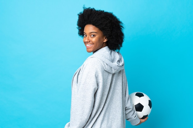 サッカーボールと青で隔離の若いアフリカ系アメリカ人女性