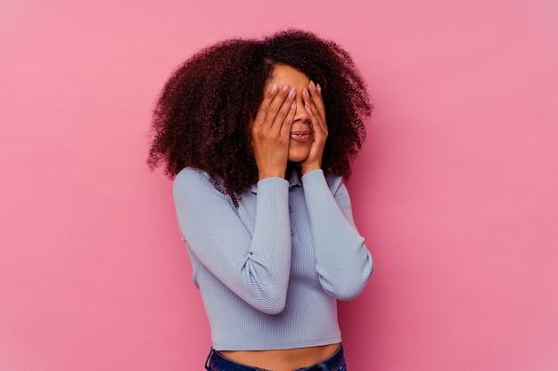 손으로 눈을 덮고 두려워 분홍색 배경에 고립 된 젊은 아프리카 계 미국인 여자.