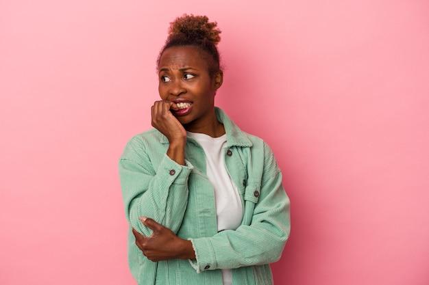 분홍색 배경에 고립되어 손톱을 물어뜯고 긴장하고 매우 불안한 젊은 아프리카계 미국인 여성.