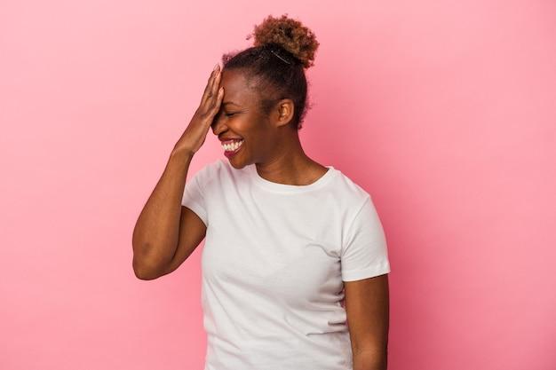 ピンクの背景で隔離された若いアフリカ系アメリカ人の女性は、恥ずかしい顔を覆って、指を介してカメラで点滅します。