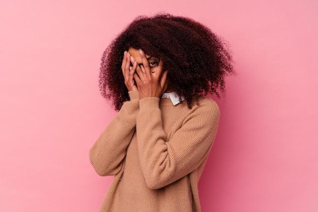 Молодая афро-американская женщина, изолированная на розовом фоне, мигает сквозь пальцы испуганно и нервно.