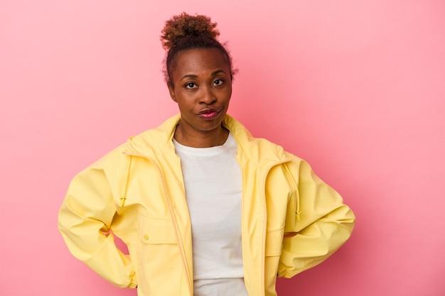 분홍색 배경에 고립된 젊은 아프리카계 미국인 여성은 뺨을 불고 피곤한 표정을 짓고 있습니다. 표정 개념입니다.