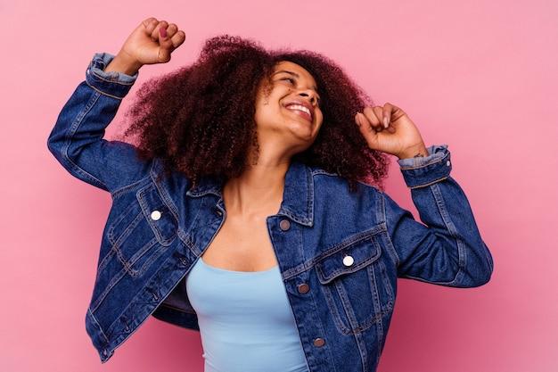 특별 한 날을 축 하하는 분홍색 배경에 고립 된 젊은 아프리카 계 미국인 여자 점프 하 고 에너지로 팔을 올립니다.