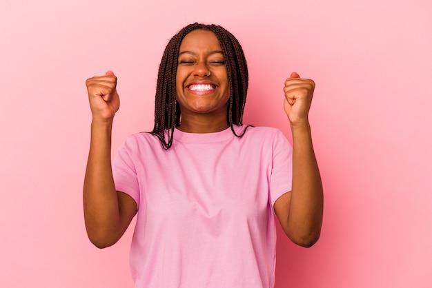 勝利、情熱と熱意、幸せな表現を祝うピンクの背景に分離された若いアフリカ系アメリカ人女性。