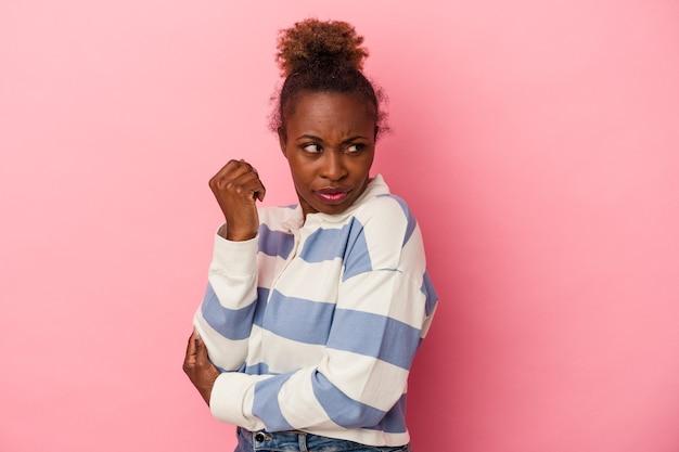 ピンクの背景に孤立した若いアフリカ系アメリカ人の女性は混乱し、疑わしく、不安を感じています。