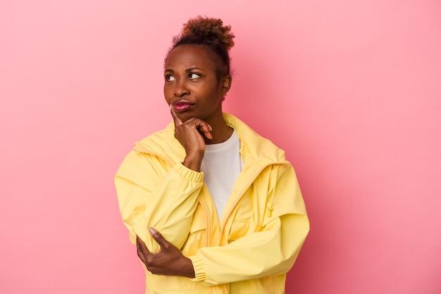 ピンクの背景に孤立した若いアフリカ系アメリカ人女性は、ビジネスの方法を考え、戦略を計画し、考えています。
