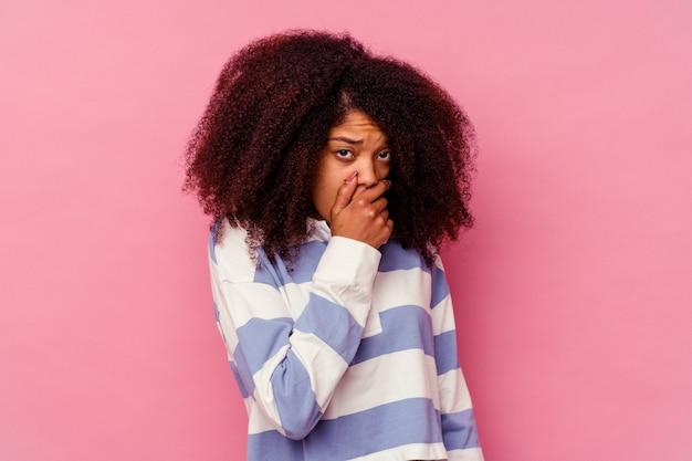 걱정 찾고 손으로 입을 덮고 분홍색 배경에 고립 된 젊은 아프리카 계 미국인 여자.