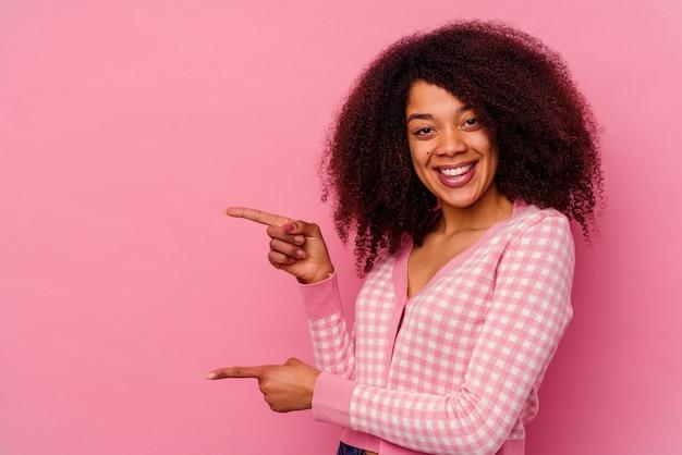 분홍색 배경에 고립 된 젊은 아프리카 계 미국인 여자는 멀리 집게 손가락으로 가리키는 흥분.