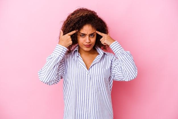 Молодая афро-американская женщина, изолированная на розовом фоне, сосредоточилась на задаче, держа указательные пальцы, указывая головой.