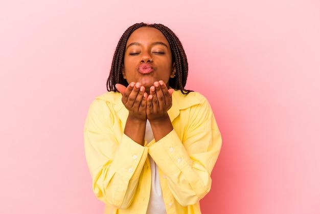 ピンクの背景に孤立した若いアフリカ系アメリカ人の女性は、唇を折り、手のひらを持って空気のキスを送信します。