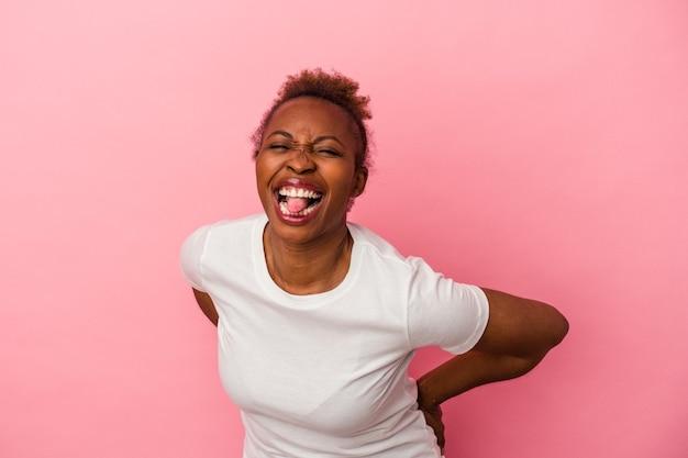 ピンクの背景に分離された若いアフリカ系アメリカ人女性は、面白いとフレンドリーな舌を突き出しています。
