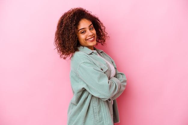 행복 하 고 웃 고 쾌활 한 분홍색 배경에 고립 된 젊은 아프리카 계 미국인 여자.