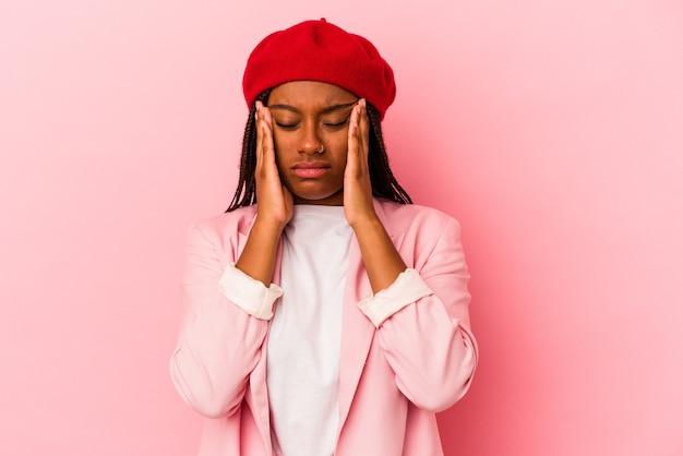 顔の正面に触れて、頭痛を持っているピンクの背景に分離された若いアフリカ系アメリカ人の女性。