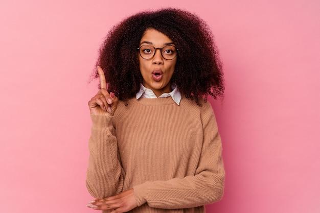 몇 가지 좋은 아이디어, 창의성의 개념을 갖는 분홍색 배경에 고립 된 젊은 아프리카 계 미국인 여자.