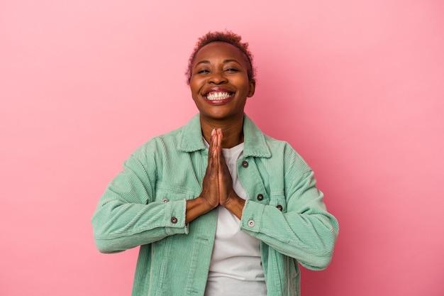 ピンクの背景に孤立した若いアフリカ系アメリカ人女性は、口の近くで祈って手をつないで、自信を持っています。