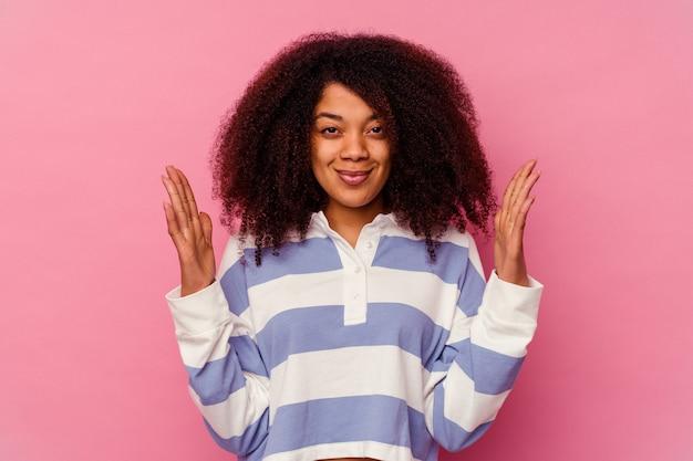 젊은 아프리카 계 미국인 여자는 웃 고 자신감, 집게 손가락으로 뭔가 조금 들고 분홍색 배경에 고립.