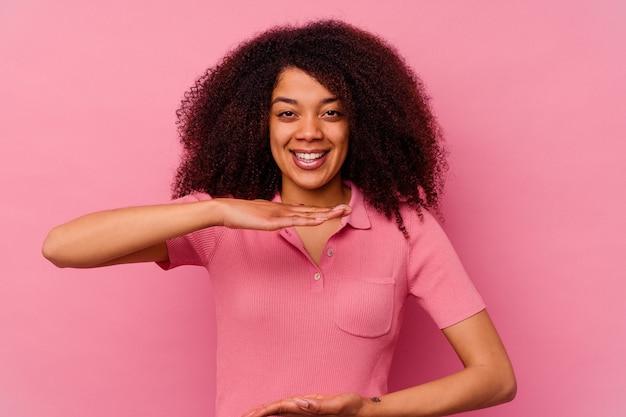 제품 프레 젠 테이 션 양손으로 뭔가 들고 분홍색 배경에 고립 된 젊은 아프리카 계 미국인 여자.