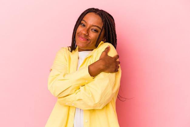 Молодая афро-американская женщина, изолированная на розовом фоне, обнимает, беззаботно улыбается и счастлива.