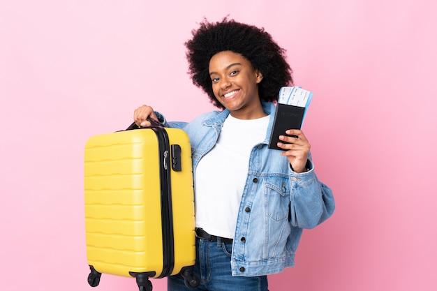 スーツケースとパスポートの休暇でピンクの背景に分離された若いアフリカ系アメリカ人女性