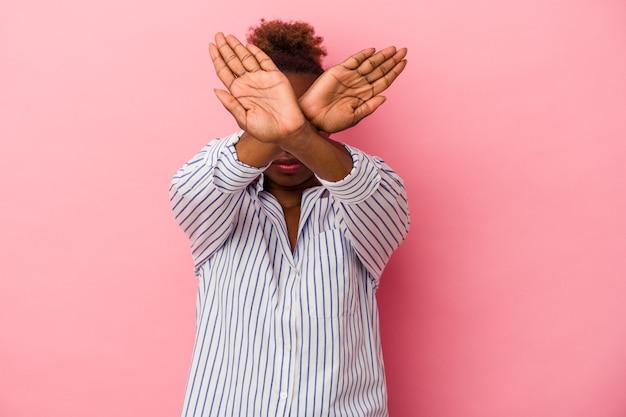 Молодая афро-американская женщина, изолированные на розовом фоне, держа скрещенными руками, концепцию отрицания.