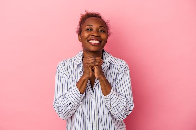 Молодая афро-американская женщина, изолированная на розовом фоне, держит руки под подбородком, счастливо смотрит в сторону.