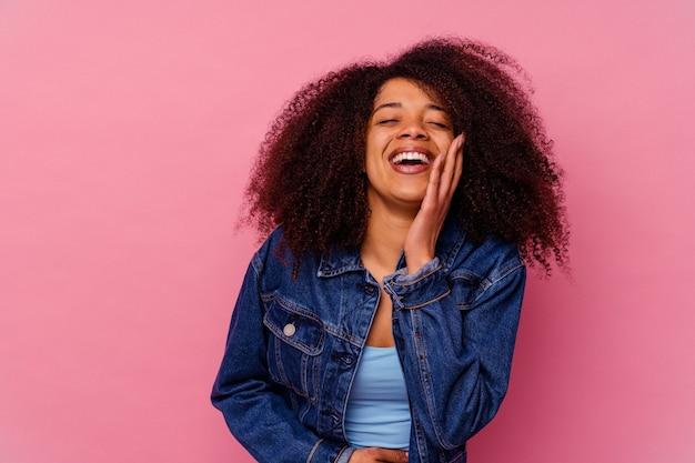 분홍색 배경에 고립 된 젊은 아프리카 계 미국인 여자는 행복 하 게 웃음과 뱃속에 손을 유지하는 재미있다.