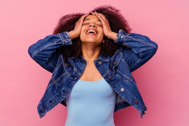 분홍색 배경에 고립 된 젊은 아프리카 계 미국인 여자는 즐겁게 손을 머리에 유지 웃음. 행복 개념.