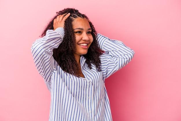Молодая афро-американская женщина, изолированная на розовом фоне, радостно смеется, держа руки на голове. концепция счастья.