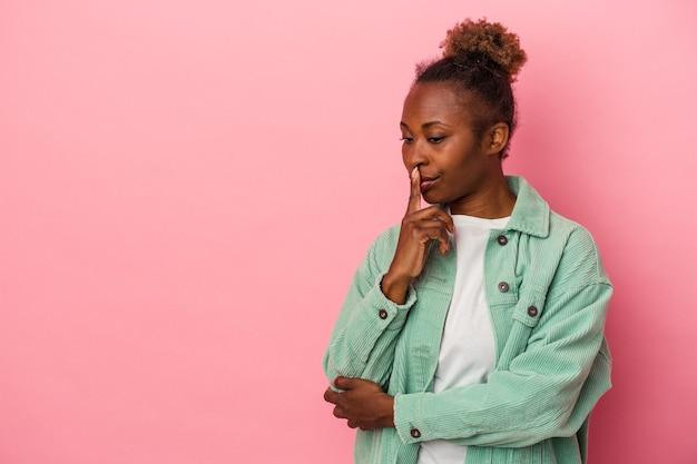 疑わしいと懐疑的な表現で横向きに見えるピンクの背景に分離された若いアフリカ系アメリカ人女性。