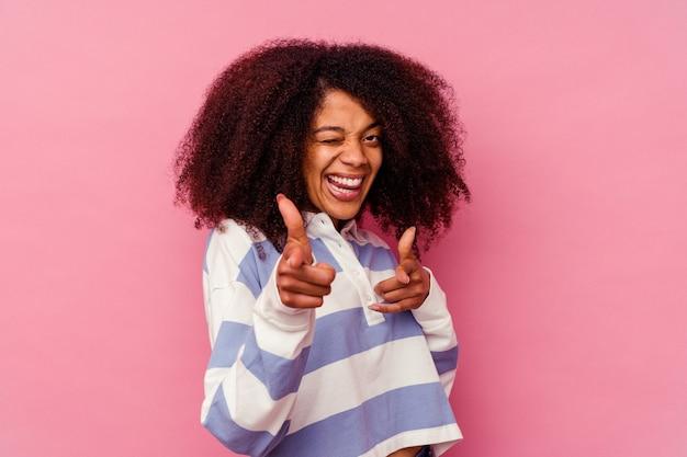 손가락으로 앞을 가리키는 분홍색 배경에 고립 된 젊은 아프리카 계 미국인 여자.
